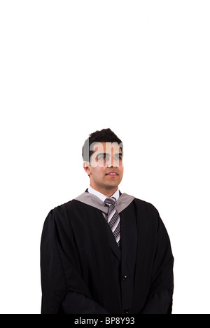 Young Asian graduate in graduation gown looking up against a white background - Stock Photo