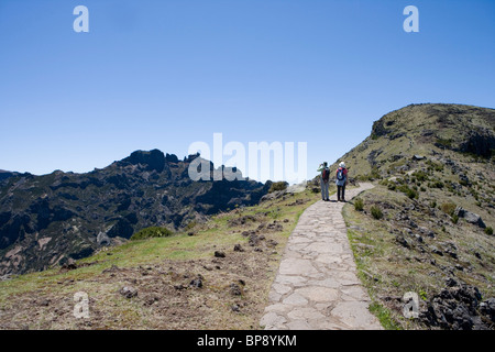 Two hikers on a trail to the Pico Ruivo Summit, Achada do Teixeira, Madeira, Portugal - Stock Photo