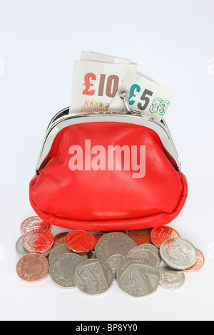 Studio, England, UK, Britain Red money purse containing British ten and five pound notes with some coins spilling - Stock Photo