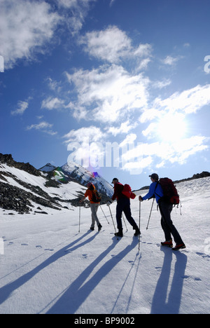 Three mountain hikers ascending to mount Hochfeiler, Zillertal Alps, South Tyrol, Italy - Stock Photo