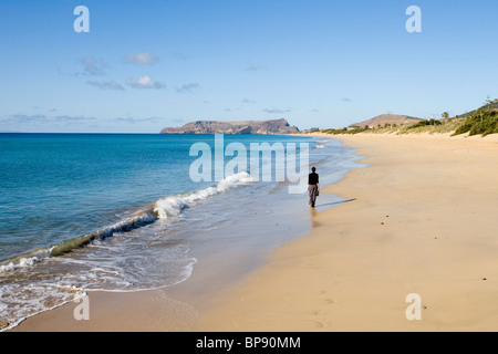 Woman strolling along Porto Santo Beach, Porto Santo, near Madeira, Portugal - Stock Photo