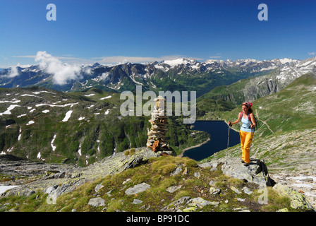 Woman near cairn above reservoir Lago della Sella, Gotthard range, Canton of Ticino, Switzerland - Stock Photo