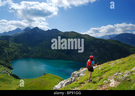 Woman hiking above reservoir Lago Ritom, Ticino Alps, Canto of Ticino, Switzerland - Stock Photo