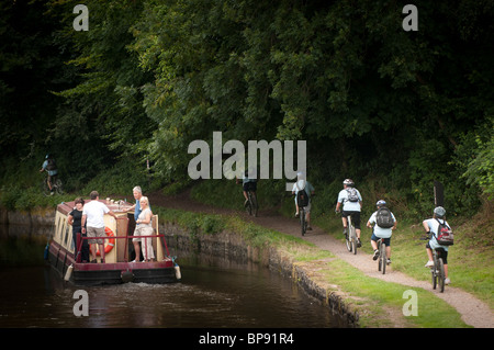 Cyclists on the towpath and a narrowboat on the Monmouthshire and Brecon Canal, South Wales UK - Stock Photo