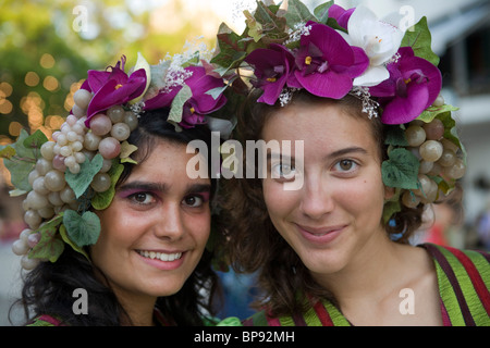 Two young women in colourful costumes at the Madeira Wine Festival, Funchal, Madeira, Portugal - Stock Photo