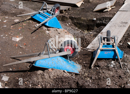 Three blue wheelbarrows at an archeological excavation ground. - Stock Photo
