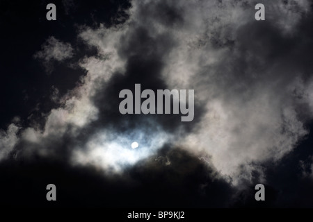 The sun shines from behind storm clouds - Stock Photo
