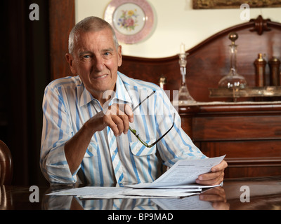 Smiling elderly man sitting at a desk looking through bills