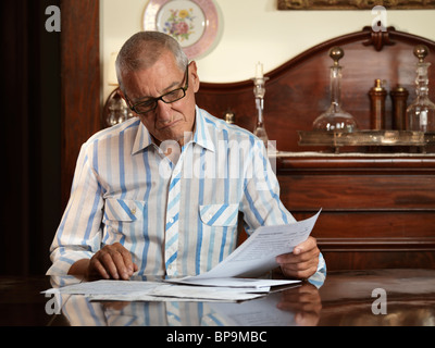 Elderly man sitting at a desk looking through bills with unhappy expression on his face