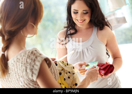 Young brunette woman paying for goods in shop - Stock Photo