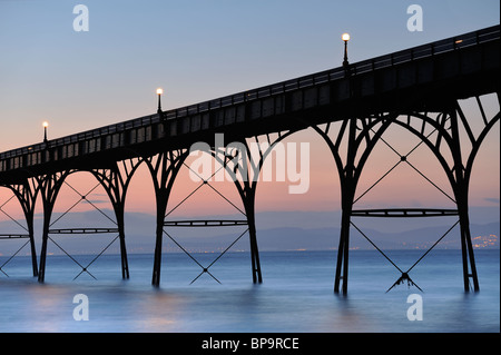 An abstract of the walkway of Clevedon Pier, North Somerset, silhouetted against a pastel sky after sunset. - Stock Photo
