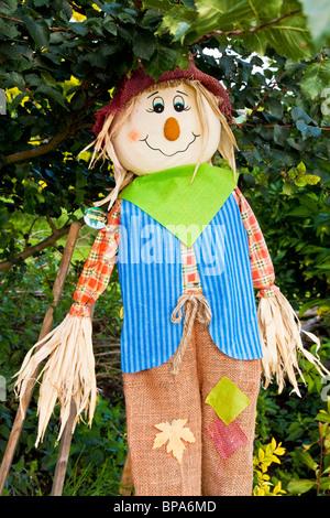 A stuffed scarecrow on a stick under a bush