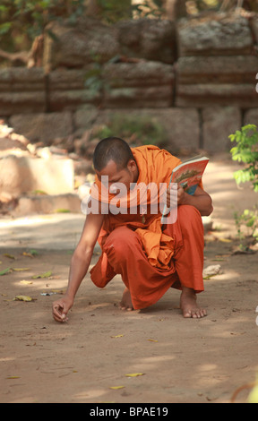 Buddhist monk is writing in the sand - Stock Photo