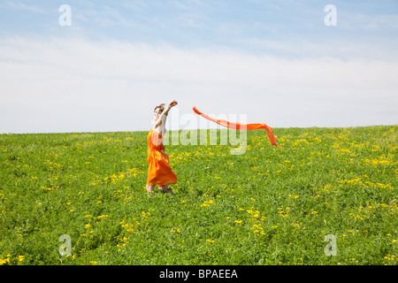 Young woman wearing an orange dress outdoor on a spring day - Stock Photo