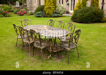 Old fashioned gold colored cast iron table and eight chairs on formal lawn - Stock Photo