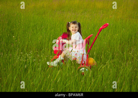 The comical child goes across the field on a bicycle and grimace - Stock Photo
