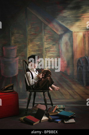 victoria, british columbia, canada; a boy posed reading old books - Stock Photo