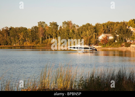 alberta, canada; a speed boat on a lift in a lake - Stock Photo