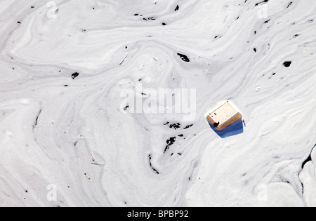 Layer of foam and waste floating on water surface - Stock Photo