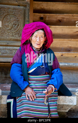 Old ethnic minority Chinese woman in Shangri-La or Zhongdian in Yunnan Province, China - Stock Photo