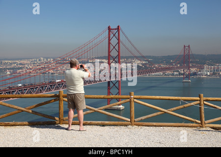 Tourist taking pictures of the Ponte 25 de Abril - Suspension bridge over the Tagus river in Lisbon, Portugal