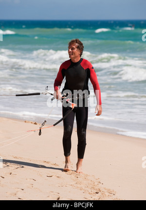 tarifa, cadiz, andalusia, spain; a man on punta paloma beach wearing a wetsuit and carrying kitesurfing equipment - Stock Photo