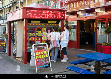 Playing gaming machines on the streets of Clacton on Sea, United Kingdom - Stock Photo