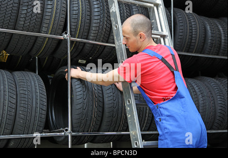 A motivated worker in a tire workshop standing on a ladder and checking the stock - Stock Photo