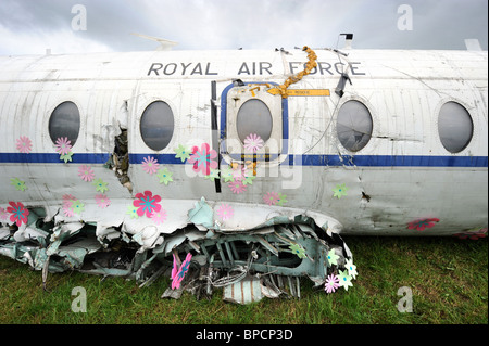 An artistically decorated old RAF plane with flowers in The Trash City area at the Glastonbury Festival site Pilton - Stock Photo
