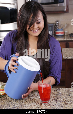 Teen pouring a glass of kool-aid - Stock Photo