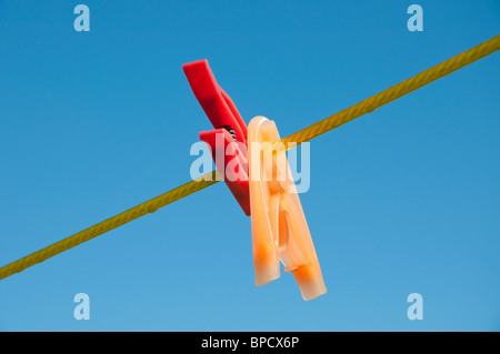 Red and yellow clothes pegs on a line, blue sky in background - Stock Photo