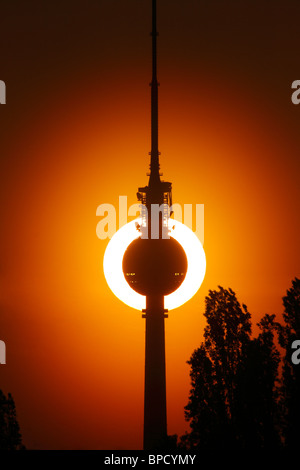 Setting sun behind the TV tower Fernsehturm, Berlin, Germany - Stock Photo