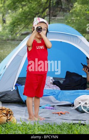 Cute girl looking at camera through telescope - Stock Photo