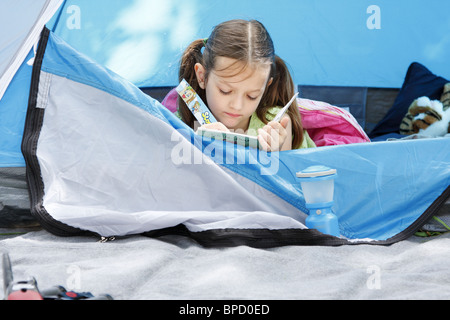Girl in tent reading a book