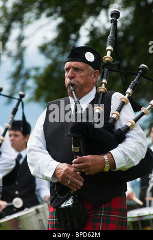 Scotsman playing the bagpipes at Stirling castle, Scotland - Stock Photo