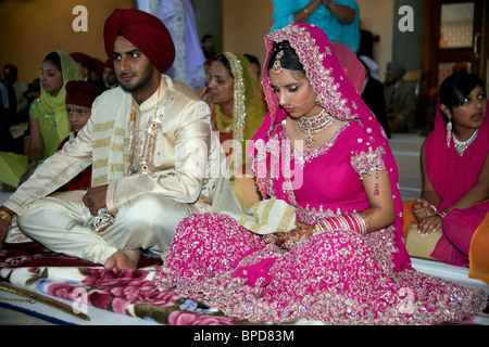 A Sikh wedding ceremony in England. Bride is holding the palla bonding her to her new husband. - Stock Photo
