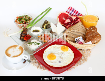 Traditional Israeli Breakfast with two fried eggs, cheeses, salad, a fresh roll orange juice and a cup of cappuccino - Stock Photo