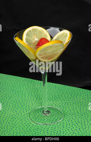 A fanciful fruit cocktail in a martini glass. A colorful background in a well composed still life. - Stock Photo
