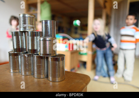 Children throwing balls at empty tins during a birthday party, Berlin, Germany - Stock Photo