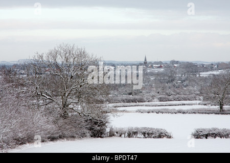 A view of a distant village across snow covered fields. - Stock Photo