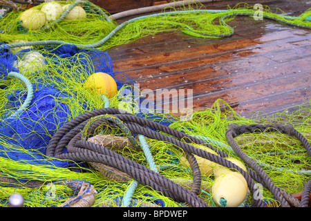 fishermen professional tackle net on boat wooden wet deck - Stock Photo