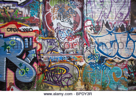 Graffiti on a wall and door in a back alley of the Fashion District near Queen West in Toronto Ontario Canada - Stock Photo