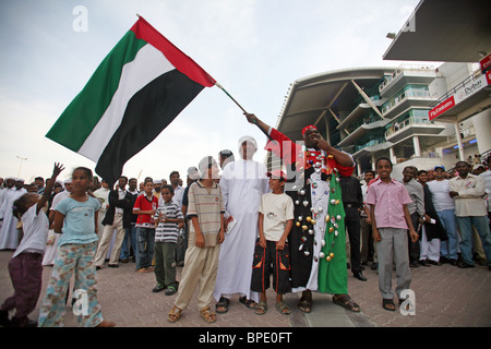 A man waving the national flag of the United Arab Emirates, Dubai - Stock Photo