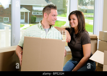 Young Couple Moving Into Their New Home Surrounded By Cardboard Boxes - Stock Photo