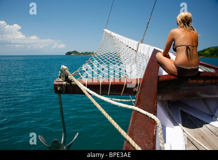 Tourists on a schooner cruising between the different beaches and islands around Parati, Rio de Janeiro State, Brazil. - Stock Photo