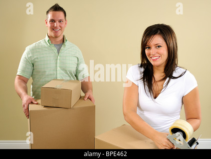 Young Couple Moving House Packing Up Boxes. (Focus is on the girl) - Stock Photo