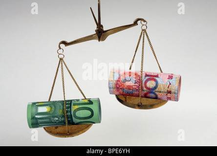 Euro and renminbi yuan banknotes on scales - Stock Photo