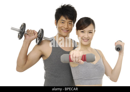 young couple holding Dumbbell - Stock Photo
