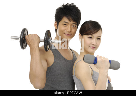young couple  lifting dumbbells  on white - Stock Photo
