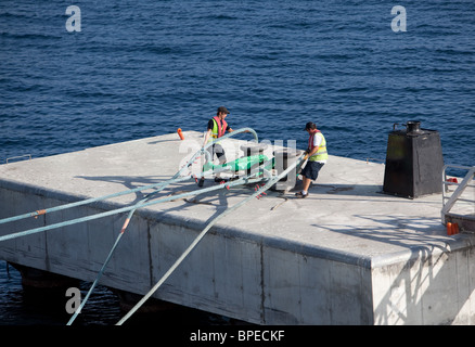 Harbour workers casting off the mooring hawser of the passenger ship Ventura Ajaccio Corsica - Stock Photo
